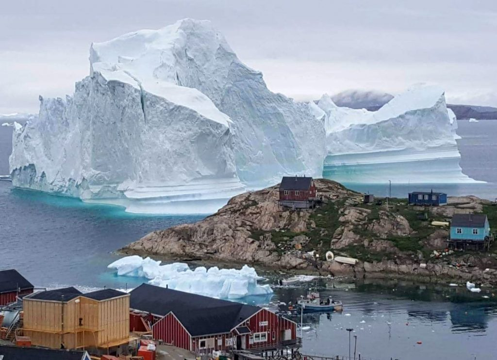 The Artic is melting much faster than expected.  This is an-iceberg-grounded-outside-the-village-of-Innarsuit, an-island-settlement-in-the-Avannaata-municipality-in-northwestern-Greenland-shown-on-July-13-2018.  CO2 is at record high despite everything